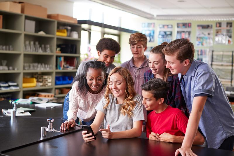 Grupa szkoła średnia ucznie Patrzeje wiadomość Na telefonie komórkowym W sala lekcyjnej fotografia stock