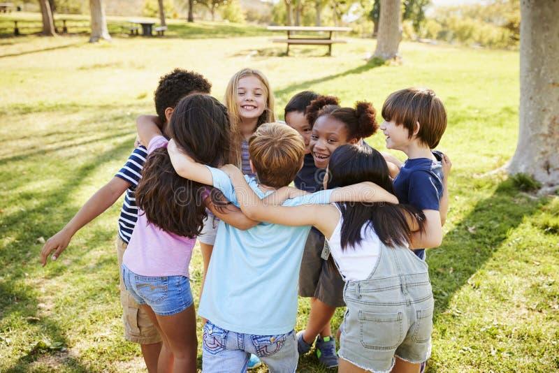 Grupa szkoła dzieciaki w skupisku outdoors, tylny widok obraz stock