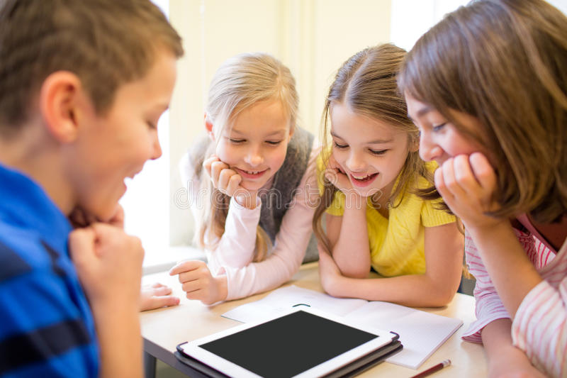 Grupa szkoła dzieciaki z pastylka komputerem osobistym w sala lekcyjnej obrazy stock