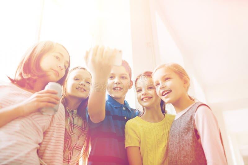 Grupa szkoła dzieciaki z smartphone i sodowanymi puszkami obraz stock