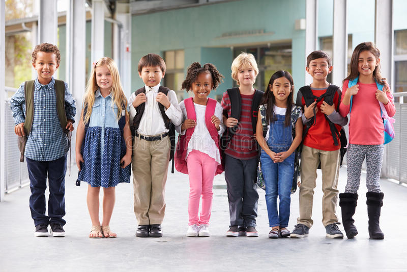 Grupa szkoła podstawowa żartuje pozycję w szkolnym korytarzu fotografia royalty free