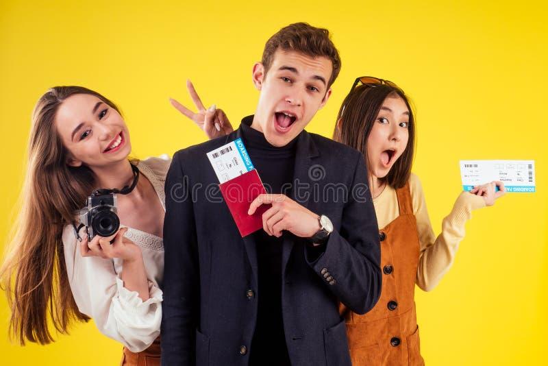 Grupa trzech śmiejących się dziewcząt i mężczyzn trzymających paszporty i bilety na przyjęcie w stylu letnim, żółte studio tła zdjęcie royalty free