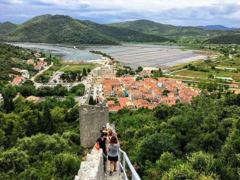 Grupa turyści chodzi w dół wzdłuż ścian Ston, w kierunku antycznego miasteczka Ston, Chorwacja pod zdjęcia stock