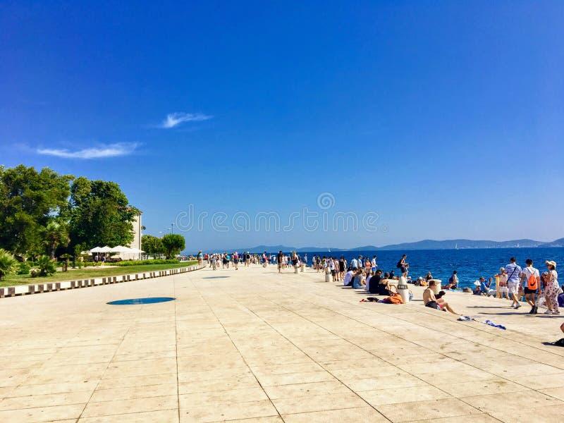 Grupa turyści wzdłuż nabrzeża w Starym miasteczku Zadar, Chorwacja obok dennych organów fotografia royalty free