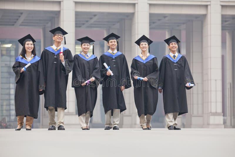 Grupa uśmiechnięci magistranci stoi dyplomy w rękach w skalowanie togach i mortarboards zdjęcie stock
