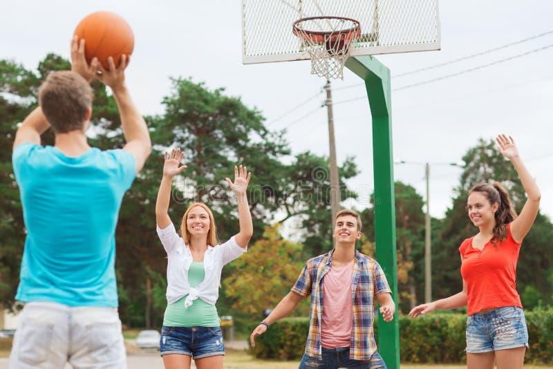Grupa uśmiechnięci nastolatkowie bawić się koszykówkę fotografia stock