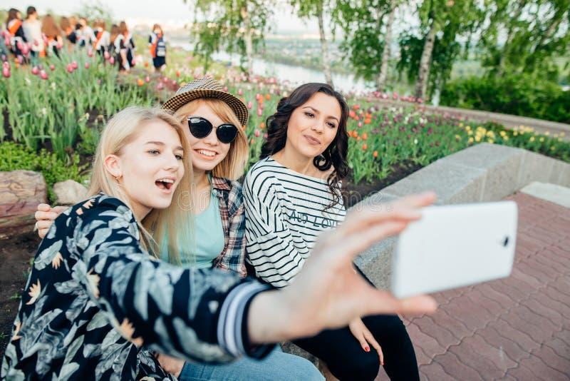 Grupa uśmiechnięci przyjaciele fotografuje selfie i bierze z smartphone obraz stock