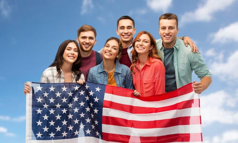Grupa uśmiechnięci przyjaciele z flagą amerykańską fotografia royalty free