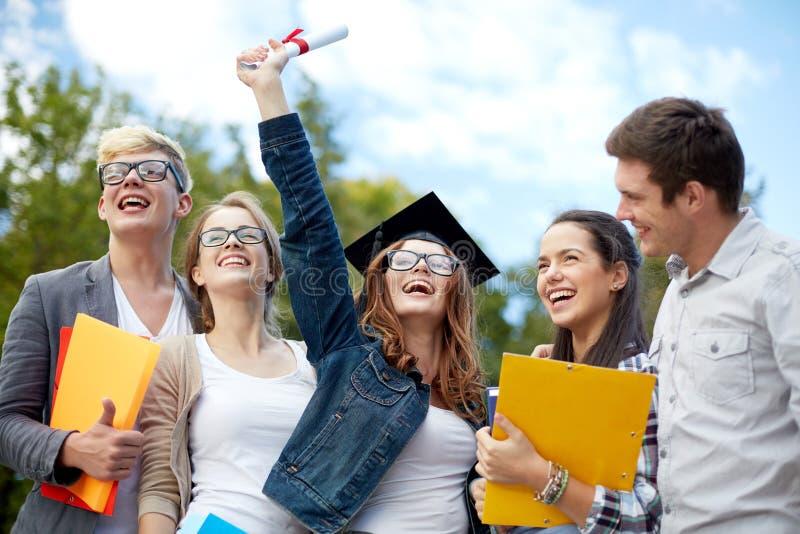 Grupa uśmiechnięci ucznie z dyplomem i falcówkami zdjęcie stock
