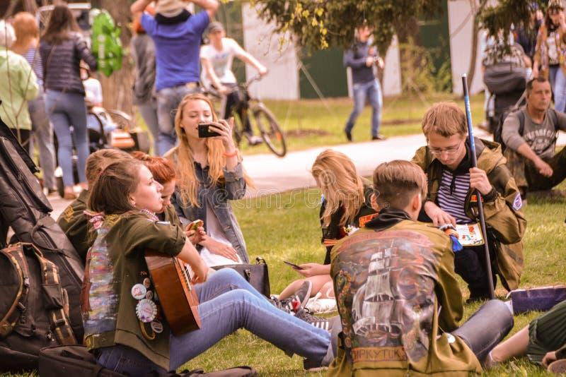 Grupa ucznie śpiewa piosenkę, odpoczywa na gazonie podczas świętowania zwycięstwo dzień na 9 może 2017 w mieście Irkut obrazy royalty free