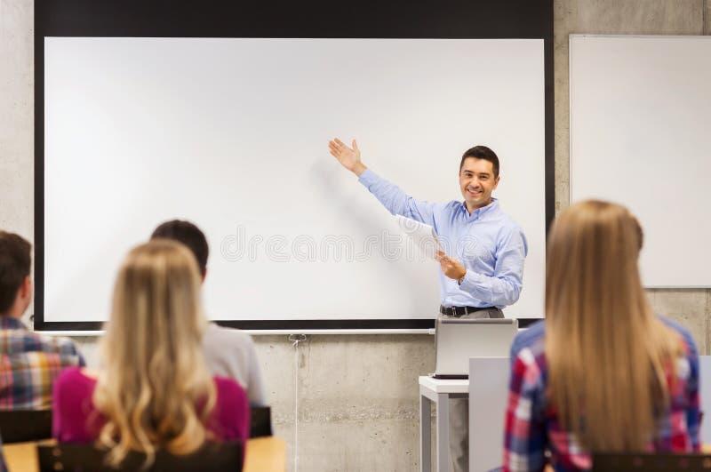 Grupa ucznie i uśmiechnięty nauczyciel z notepad obraz royalty free
