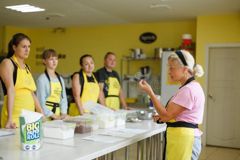 Grupa ucznie słucha kobieta szefa kuchni kulinarną lekcję obrazy stock