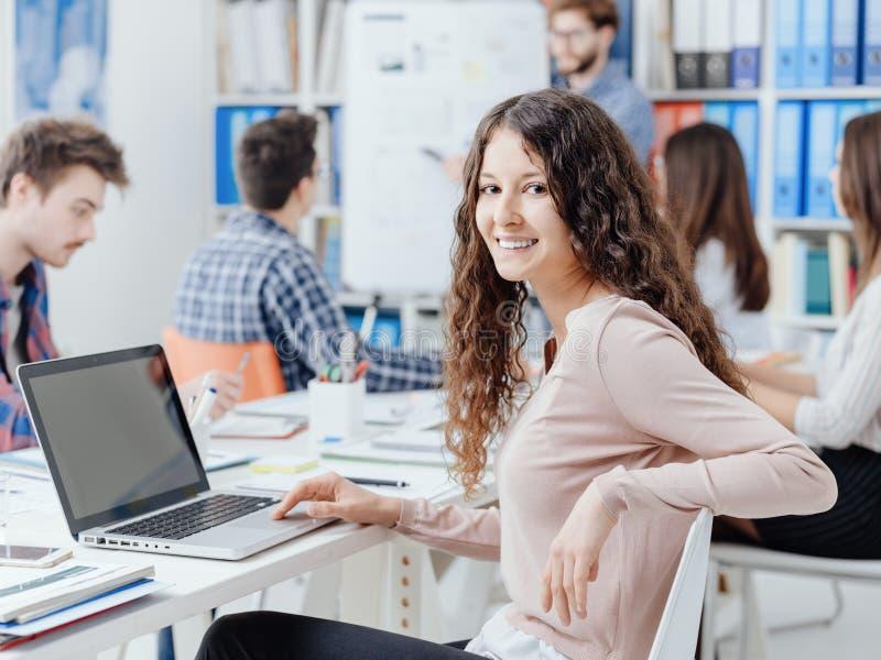 Grupa ucznie studiuje wpólnie i uśmiechnięta dziewczyna zdjęcie stock