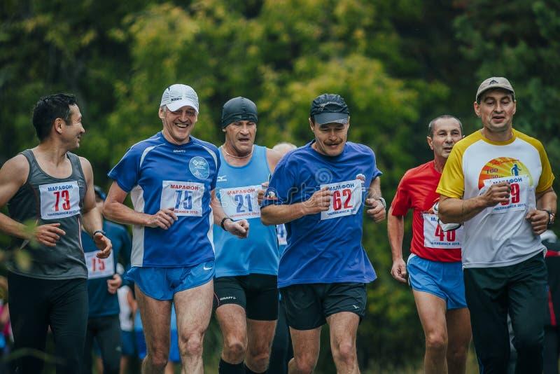 Grupa w średnim wieku joggers biega w parku zdjęcia stock