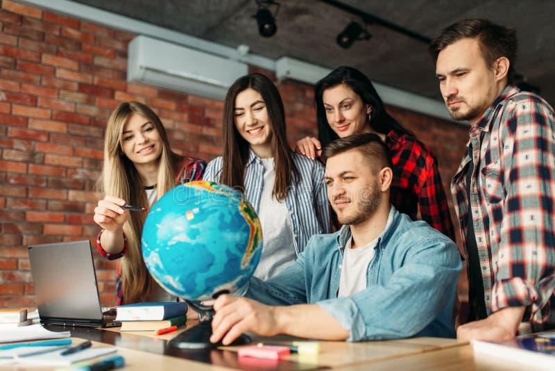 Grupa wysokiej szkoły ucznie patrzeje kulę ziemską zdjęcia royalty free