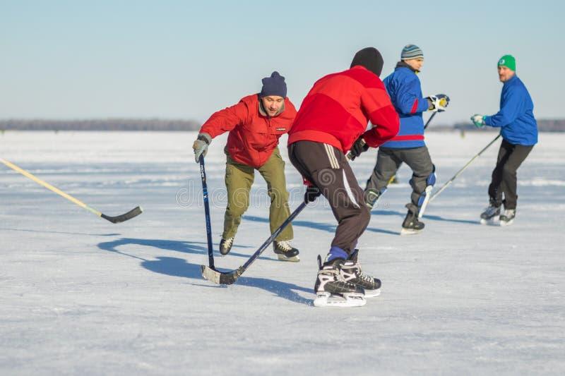 Grupa zwyczajni ludzi bawić się hokeja na zamarzniętym rzecznym Dnepr w Ukraina obrazy stock