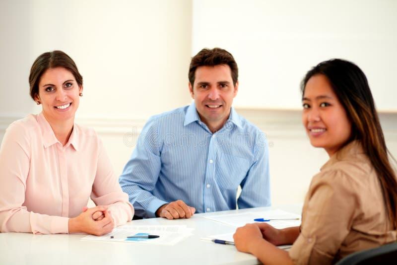 Grupo étnico ejecutivo atractivo que sonríe en usted fotografía de archivo libre de regalías