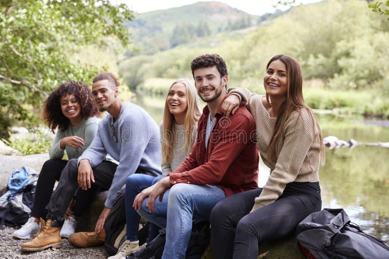 Grupo étnico multi de cinco amigos adultos jovenes que toman una rotura que se sienta en rocas por una corriente durante un alza, foto de archivo