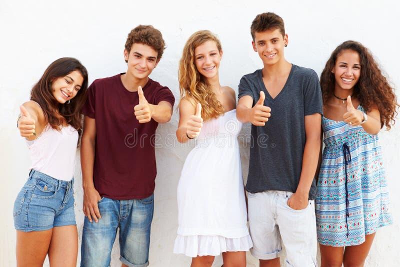 Grupo adolescente que inclina-se contra a parede que dá os polegares acima fotografia de stock