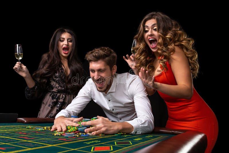 Grupo adulto que celebra al amigo que gana en la ruleta foto de archivo libre de regalías