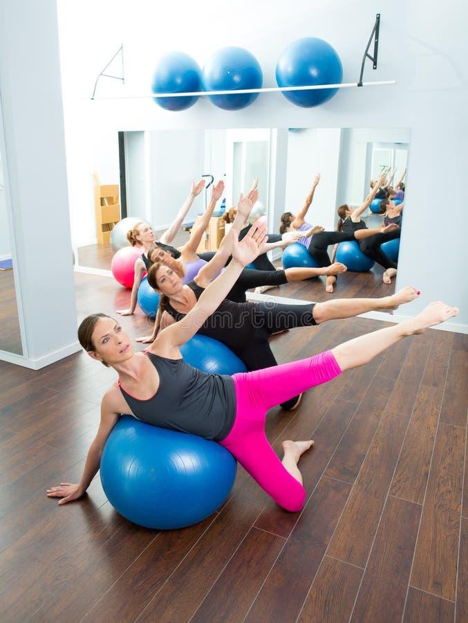 Grupo aerobio de las mujeres de Pilates con la bola de la estabilidad imagenes de archivo
