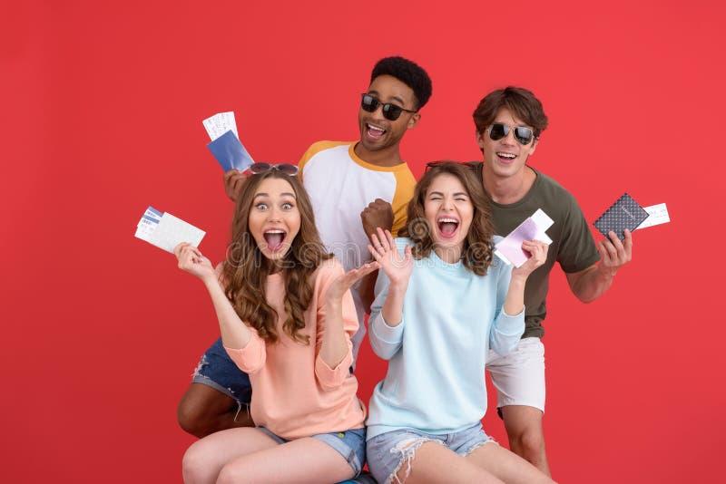 Grupo alegre de amigos que celebran pasaportes y boletos imágenes de archivo libres de regalías