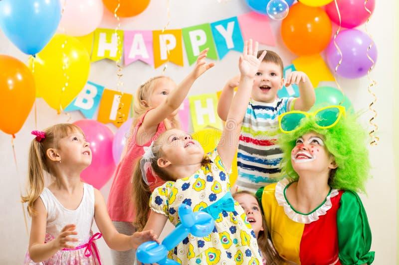 Grupo alegre de los niños que celebra la fiesta de cumpleaños imagen de archivo