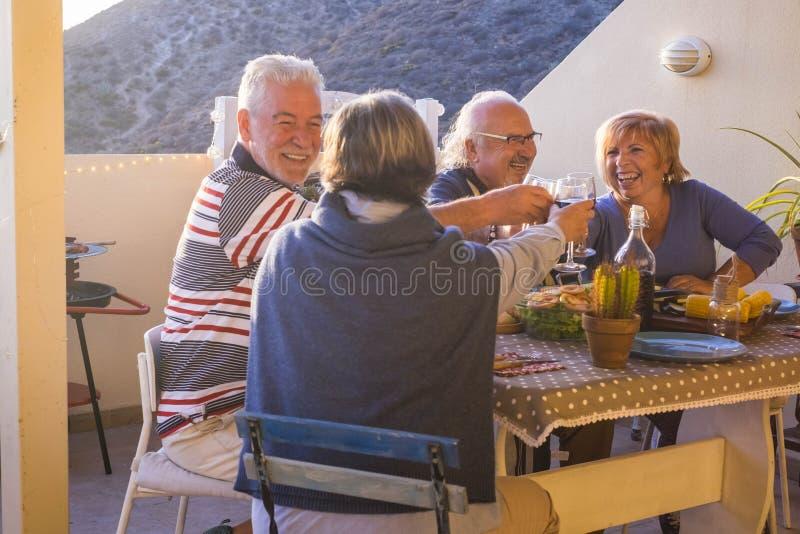 Grupo alegre de pares adultos que têm elogios do divertimento junto com vinho que come um alimento da grade no activyt do lazer d fotografia de stock royalty free