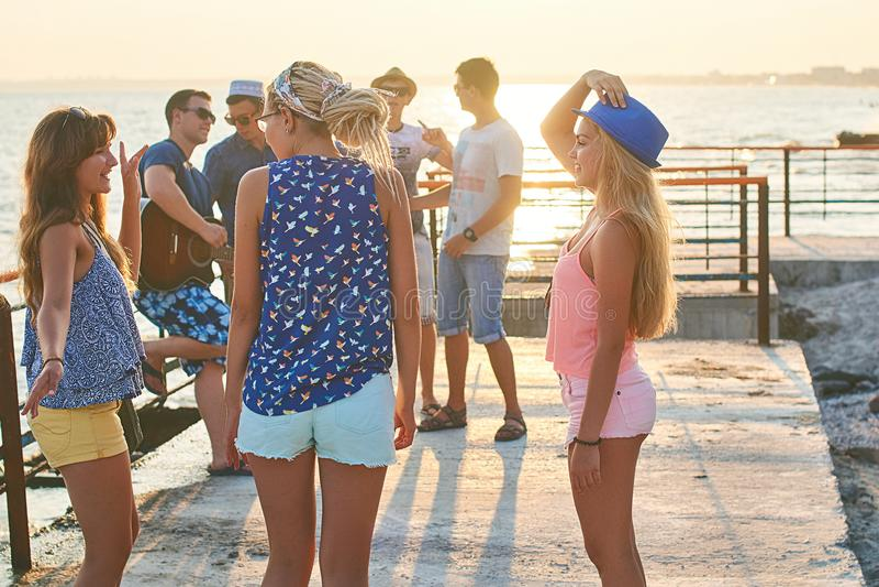 Grupo alegre y despreocupado de amigos que cuelgan hacia fuera en la playa soleada del verano en sus vacaciones fotos de archivo libres de regalías