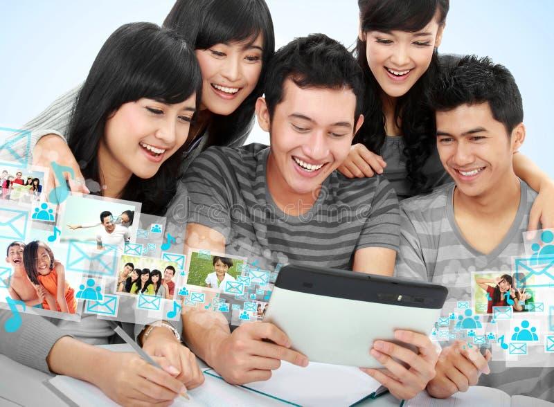 Grupo amigável de estudantes com PC da tabuleta fotos de stock