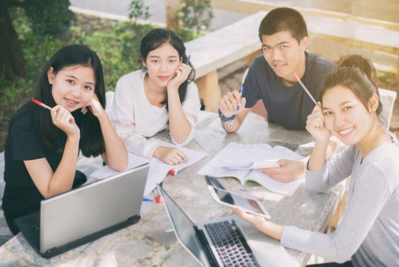 Grupo asiático de estudantes que sorriem e que compartilham com as ideias para w imagens de stock