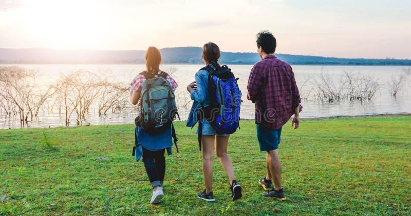 Grupo asiático de gente joven que camina con las mochilas de los amigos que camina junto y que mira el mapa y que toma la cámara  fotos de archivo