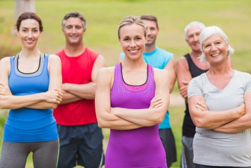 Grupo atlético feliz que sonríe en la cámara con las manos cruzadas fotos de archivo