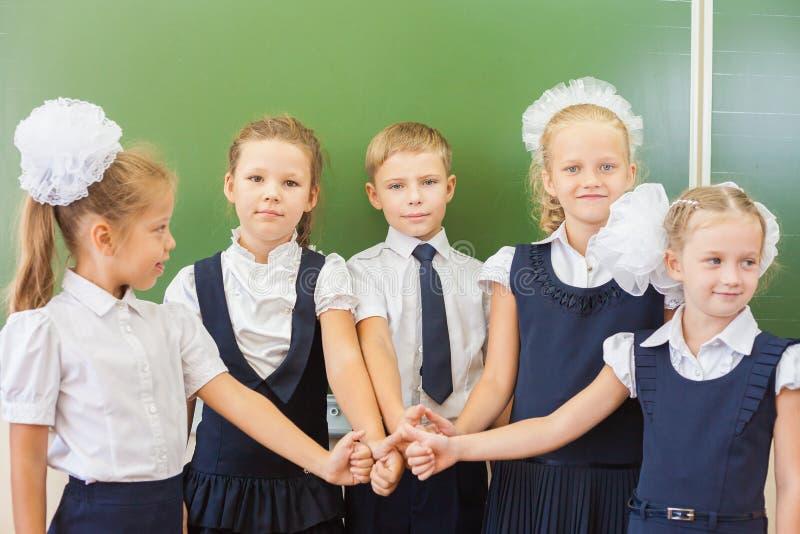 Grupo bem sucedido de crianças na escola com o polegar acima do gesto foto de stock