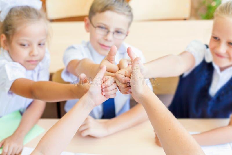 Grupo bem sucedido de crianças na escola com o polegar acima do gesto imagem de stock royalty free