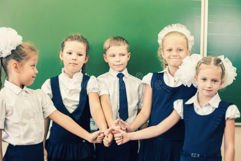Grupo bem sucedido de crianças na escola com o polegar acima do gesto imagem de stock