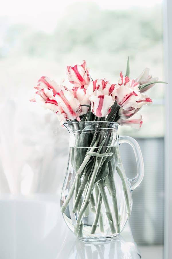 Grupo bonito das tulipas no jarro de vidro na tabela branca na janela Flores no design de interiores HOME acolhedor foto de stock