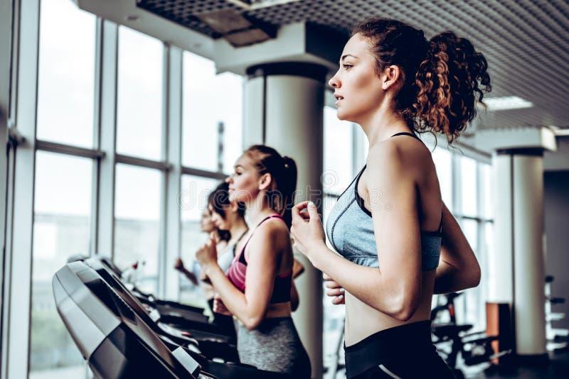 Grupo bonito de amigos das jovens mulheres que exercitam em uma escada rolante no gym moderno brilhante imagens de stock