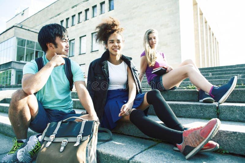 Grupo bonito de teenages na constru??o da universidade com huggings dos livros, estilo de vida real dos estudantes das na??es da  fotografia de stock royalty free