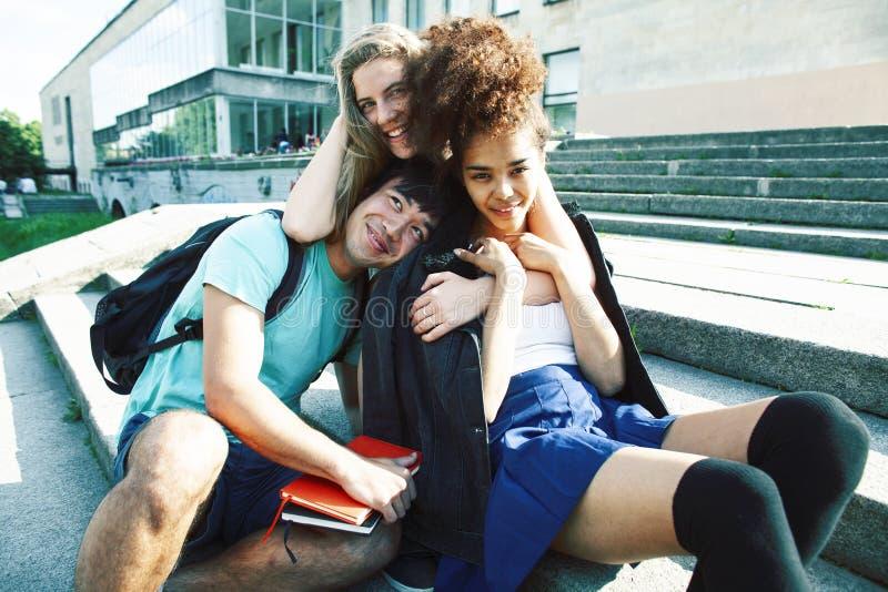 Grupo bonito de teenages na constru??o da universidade com huggings dos livros, estilo de vida real dos estudantes das na??es da  fotos de stock