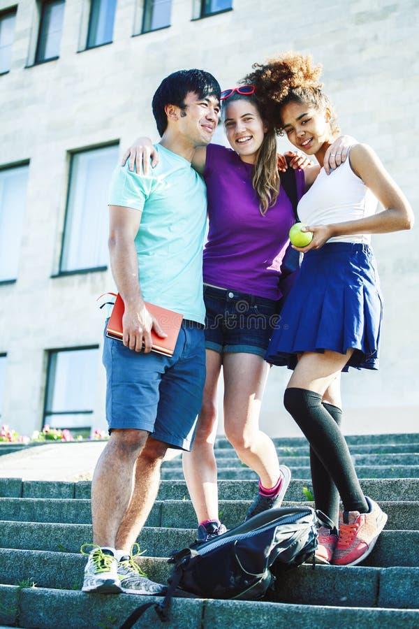 Grupo bonito de teenages na constru??o da universidade com huggings dos livros, estilo de vida real dos estudantes das na??es da  fotografia de stock