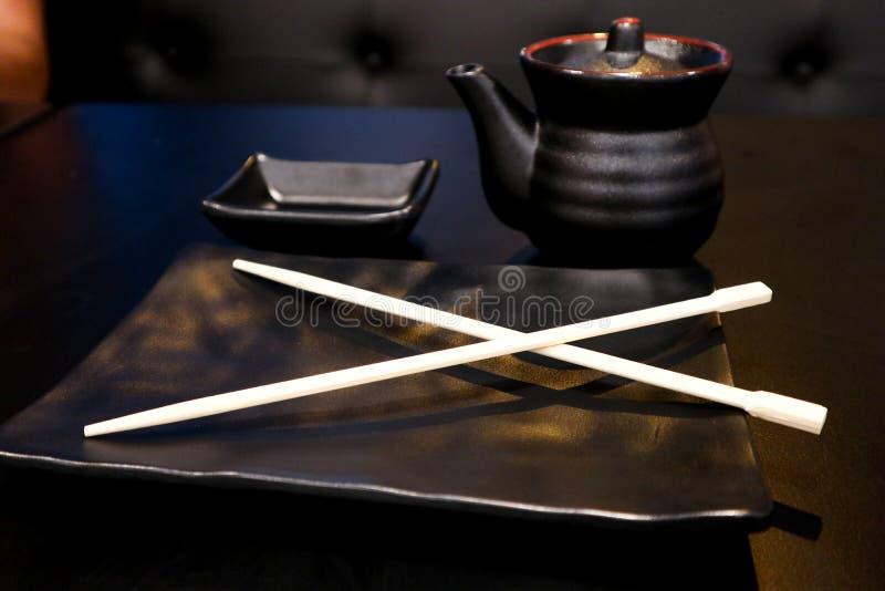 Grupo claro preto vazio para o sushi, placa com hashi japonês, pires na tabela preta imagem de stock royalty free