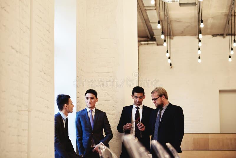 Grupo con el hombre de negocios acertado joven que muestra la pantalla del teléfono móvil a su socio mientras que ellos que tiene foto de archivo