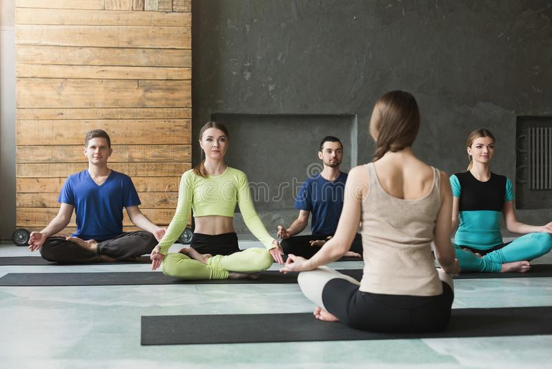 Grupo con el instructor de la yoga en club de fitness imagenes de archivo