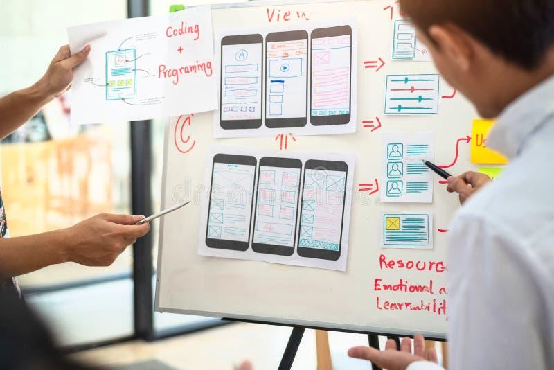Grupo creativo del diseñador de UX que trabaja sobre proyecto de aplicación móvil de cepillado con las notas pegajosas Concepto d imagenes de archivo
