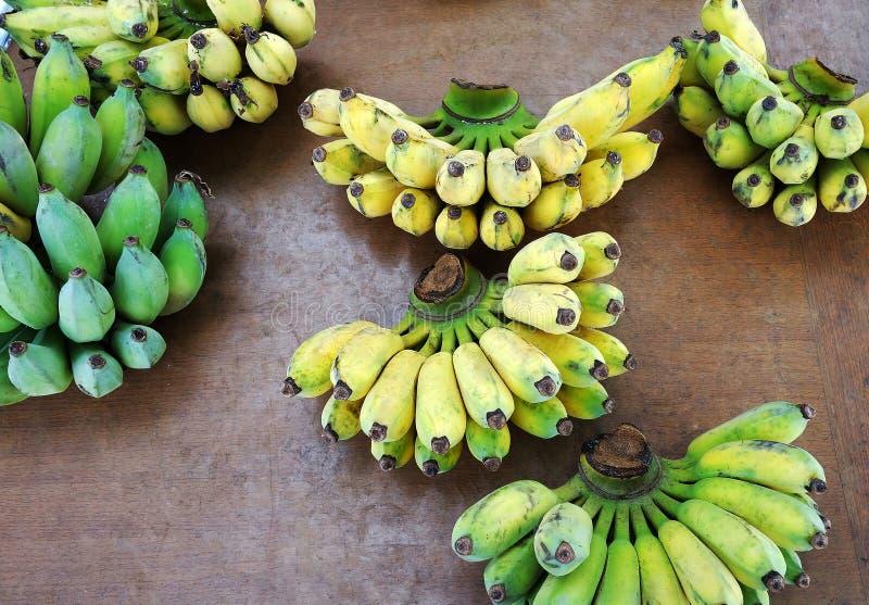 Grupo da banana cru e maduro na tabela de madeira fotografia de stock