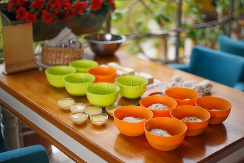 Grupo da cozinha de orrange e de copos verdes com farinha e m condensado imagem de stock