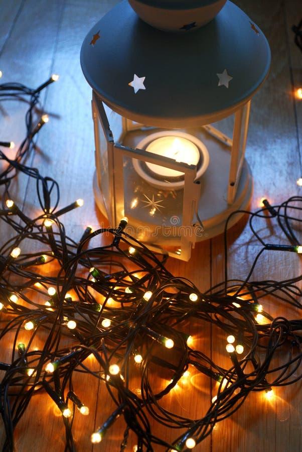 Grupo da lanterna branca com luzes de Natal e bastões de doces no assoalho de madeira imagem de stock royalty free
