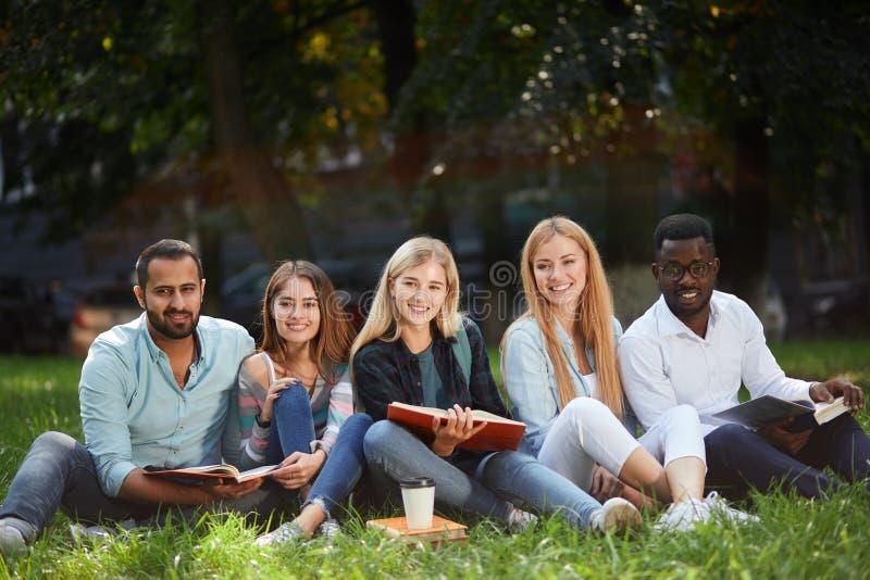 grupo da Misturado-raça de estudantes que sentam-se junto no gramado verde do campus universitário fotos de stock royalty free