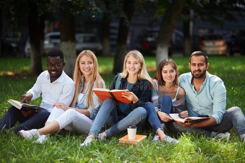 grupo da Misturado-raça de estudantes que sentam-se junto no gramado verde do campus universitário imagens de stock royalty free